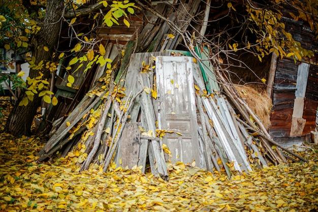 Pilha de portas velhas e tábuas de madeira no fundo da paisagem de outono