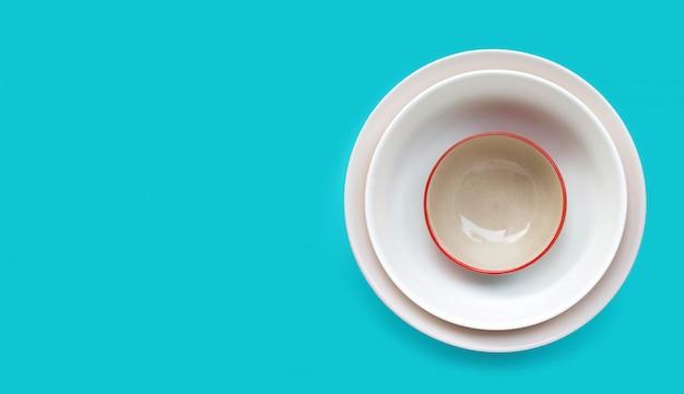 Pilha de prato e tigela sobre fundo azul.