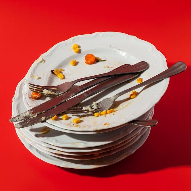 Pilha de pratos com sobras de vista alta