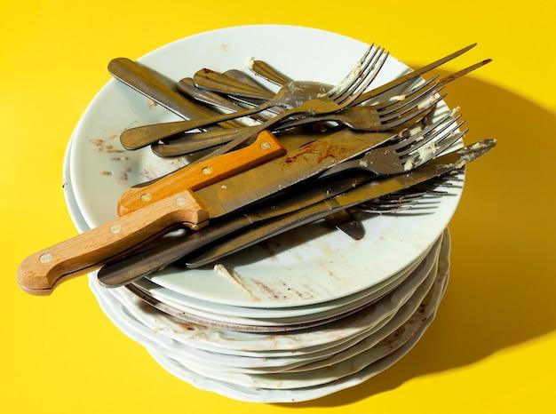 Pilha de pratos e talheres sujos