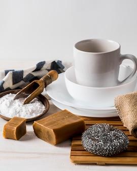 Pilha de pratos limpos e produtos de limpeza ecológicos