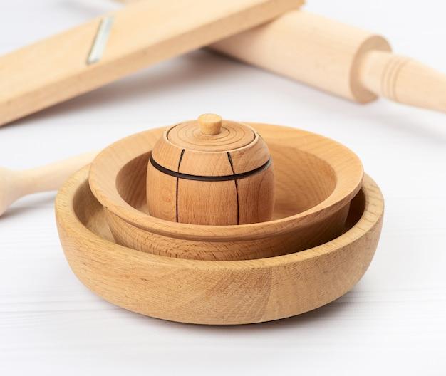 Pilha de pratos redondos de madeira vazios em uma mesa branca, close-up