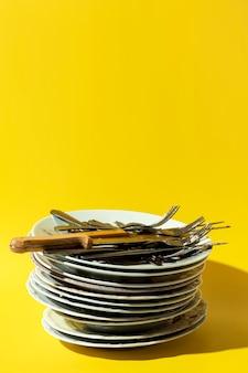Pilha de pratos sujos e cópia de talheres