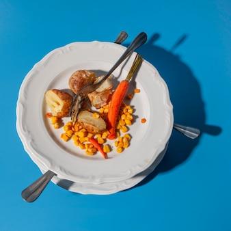 Pilha de pratos sujos e sobras de batata e milho