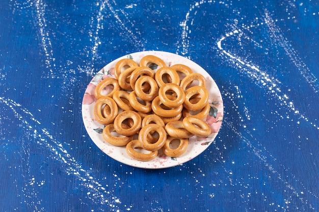 Pilha de pretzels redondos salgados colocados em um prato colorido