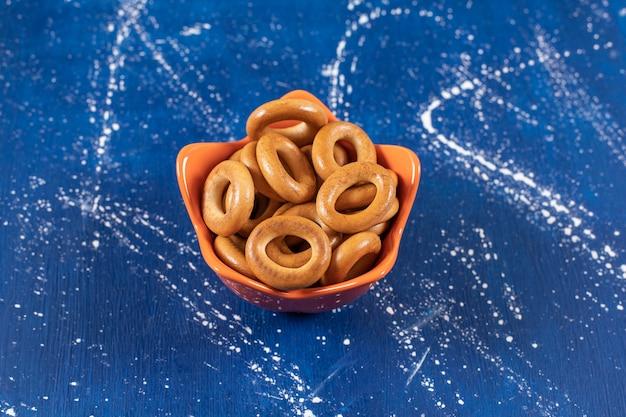 Pilha de pretzels redondos salgados colocados em uma tigela de laranja.