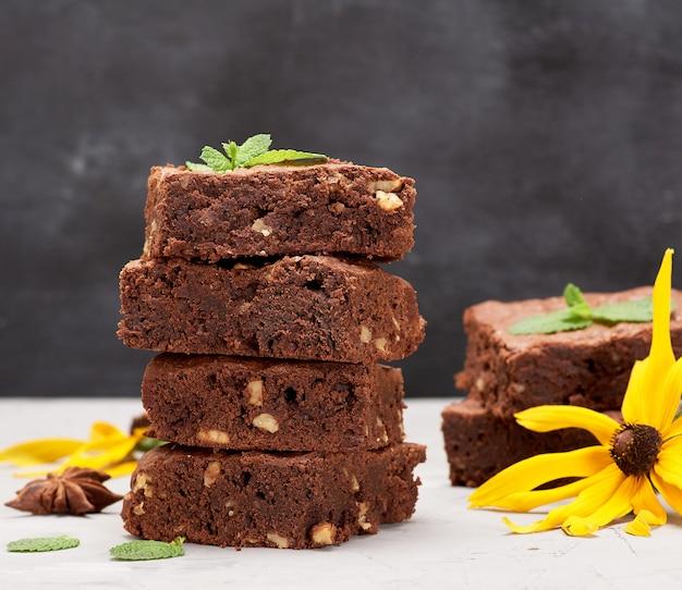 Pilha de quadrados assados pedaços de bolo de chocolate brownie com nozes em cima da mesa