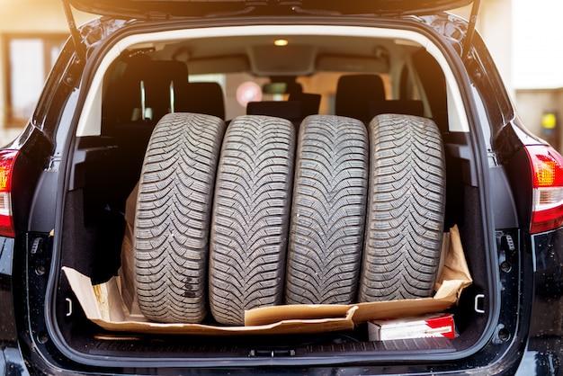 Pilha de quatro pneus usados cabendo perfeitamente no porta-malas de um carro azul.