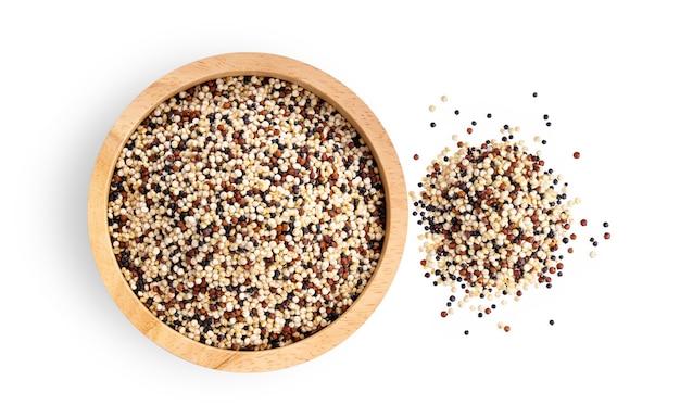 Pilha de quinoa crua mista em uma tigela de madeira, isolada no fundo branco. vista do topo