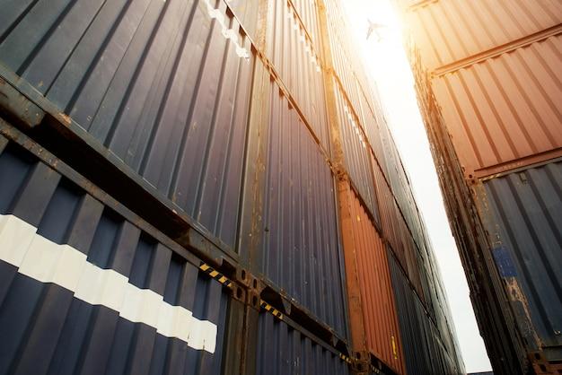 Pilha de recipientes de carga na área de importação e exportação com avião de carga no porto.