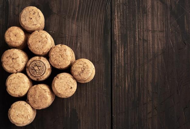 Pilha de rolhas de cortiça para garrafas de vinho e champanhe em fundo de madeira