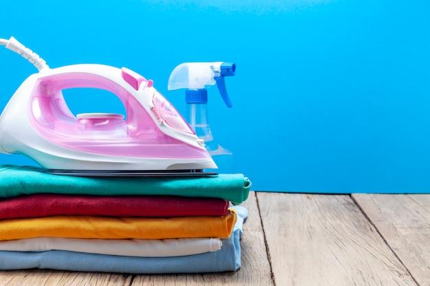 Pilha de roupas coloridas e ferros, frascos de spray, na prancha de madeira