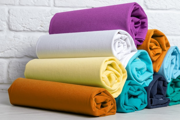 Pilha de roupas coloridas enroladas em uma mesa de madeira clara. fechar-se