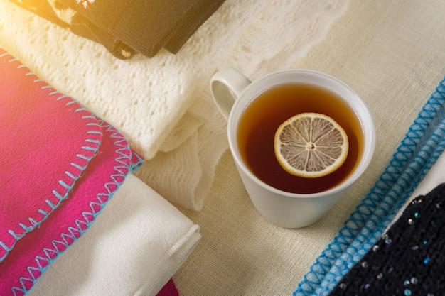 Pilha de roupas de lã quentes com uma xícara de chá