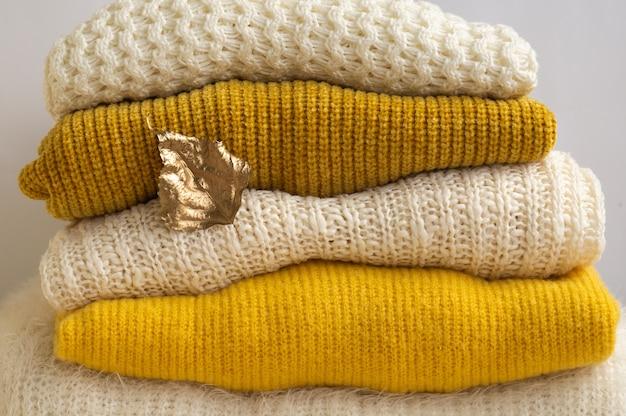 Pilha de roupas de malha com folhas de outono ouro