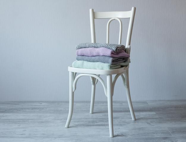 Pilha de roupas de malha confortáveis em uma cadeira de madeira