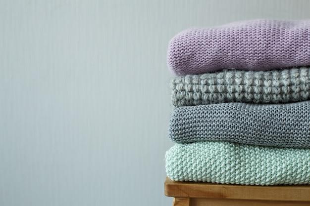 Pilha de roupas de malha confortáveis em uma escada de madeira