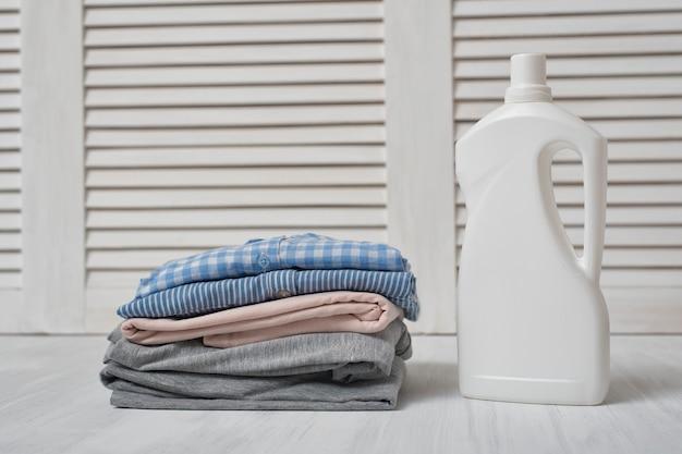 Pilha de roupas dobradas e garrafa de detergente.
