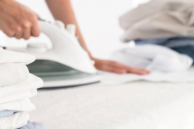 Pilha de roupas e ferro de passar roupas