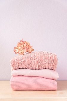 Pilha de roupas femininas de inverno ou outono. pilha de camisolas cor-de-rosa aconchegantes de malha coloridas ou pulôver na mesa de madeira.