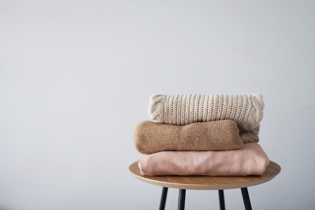 Pilha de roupas femininas limpas, recém-lavadas e cuidadosamente dobradas na mesa de madeira. suéteres quentes de outono.