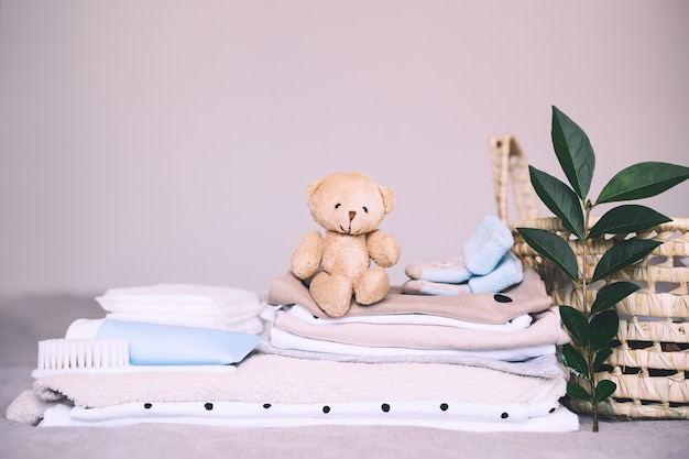 Pilha de roupas limpas de bebê, cuidados com a pele, brinquedo cosmético de ursinho de pelúcia e cesto de roupa suja para recém-nascido
