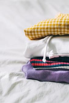 Pilha de roupas multicoloridas em uma cama branca do guarda-roupa.