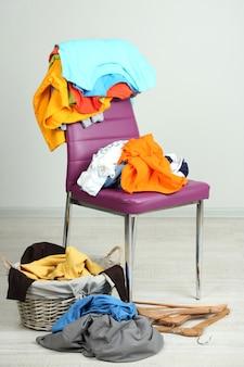 Pilha de roupas na cadeira colorida, cinza