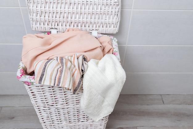 Pilha de roupas no cesto de roupa suja de vime. vista do topo