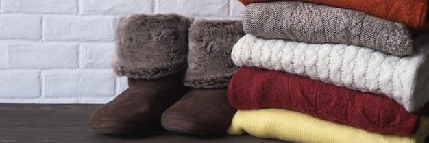 Pilha de roupas quentes de malha e chinelos coisas aconchegantes e confortáveis para a casa conceito de outono