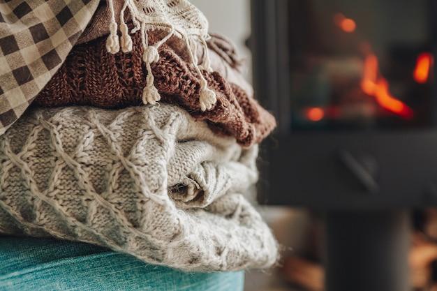 Pilha de roupas quentes em uma poltrona uma lareira de ferro