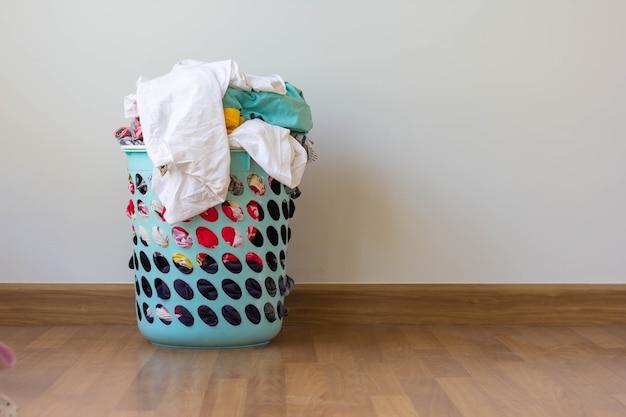 Pilha de roupas transborda cesto de roupa suja de plástico para preparações de lavagem