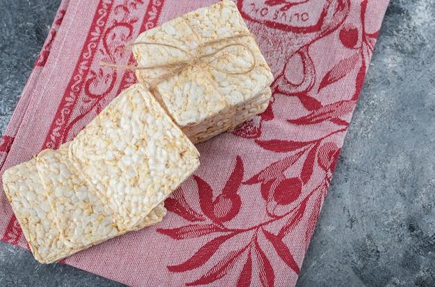 Pilha de saboroso pão estaladiço no pano vermelho.