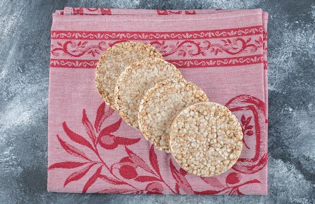Pilha de saboroso pão estaladiço redondo no pano vermelho.