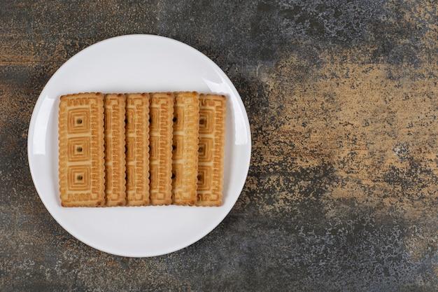 Pilha de saborosos biscoitos na chapa branca.