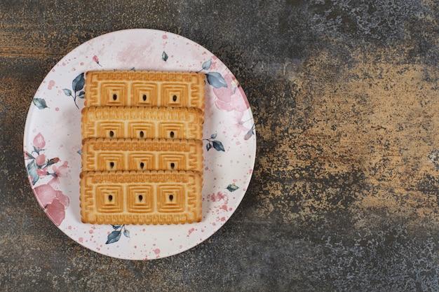 Pilha de saborosos biscoitos no prato colorido.