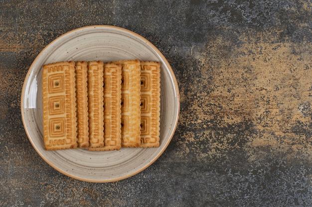 Pilha de saborosos biscoitos no prato de cerâmica.