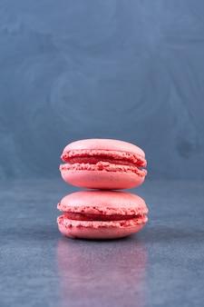 Pilha de saborosos macarons rosa colocados em uma superfície cinza