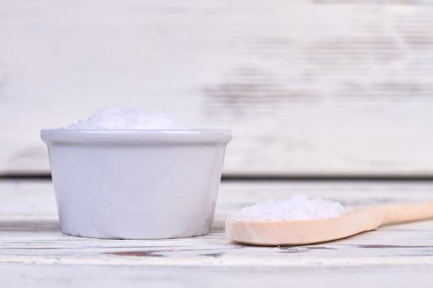 Pilha de sal branco com colher de pau rústica