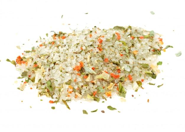 Pilha de sal do mar e uma mistura de especiarias isoladas no branco.
