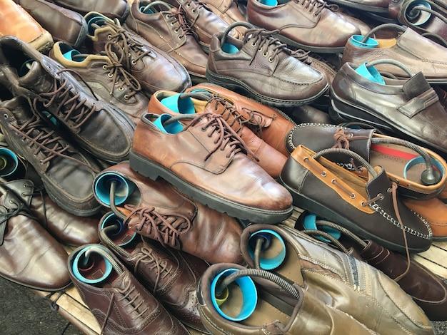 Pilha de sapatos de segunda mão na prateleira no mercado de fim de semana.