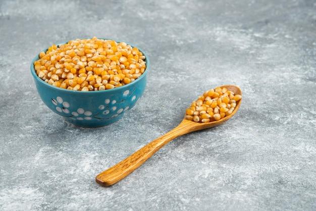 Pilha de sementes de milho cru em tigelas azuis e colher de pau.