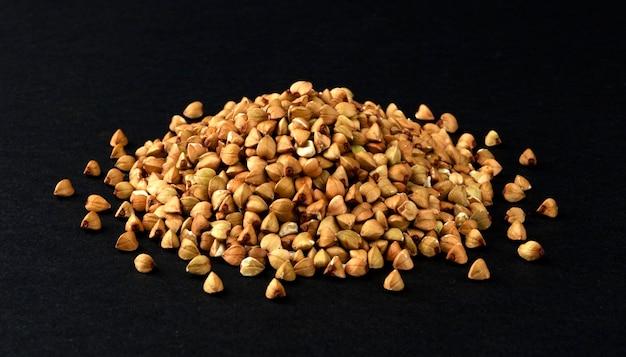 Pilha de sêmolas de trigo sarraceno verdes isoladas em fundo preto, closeup