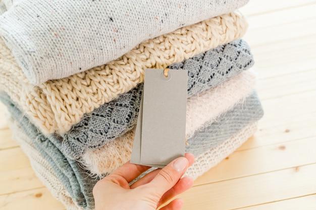 Pilha de suéter quente de malha de lã e etiqueta branca