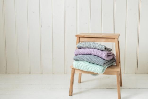 Pilha de suéteres de malha aconchegantes em uma escada de madeira