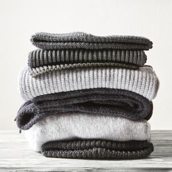 Pilha de suéteres de malha de lã cinza em uma superfície branca
