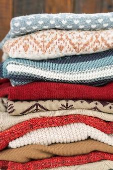 Pilha de suéteres de malha de várias cores com enfeites prontos para o outono e inverno