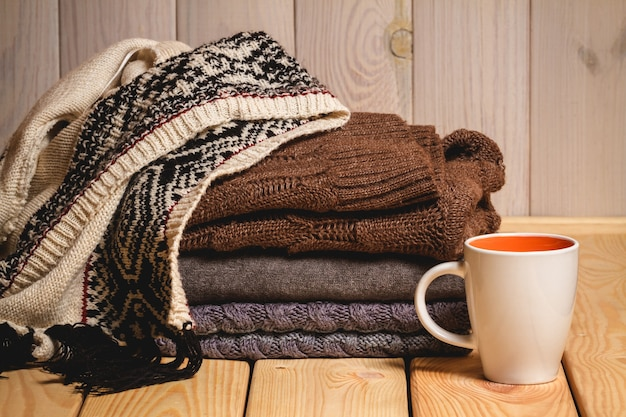 Pilha de suéteres de malha e uma xícara em uma madeira