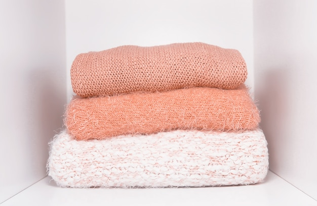 Pilha de suéteres de malha quentes de outono e inverno em uma prateleira de guarda-roupa em casa. roupas da moda moderna em tons de coral vivo.