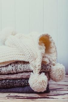 Pilha de suéteres de malha quentes, lenço e chapéu em tons de branco e cinza